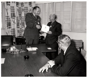 Keith shaking hands with the man on the left, receiving his 30 year certificate